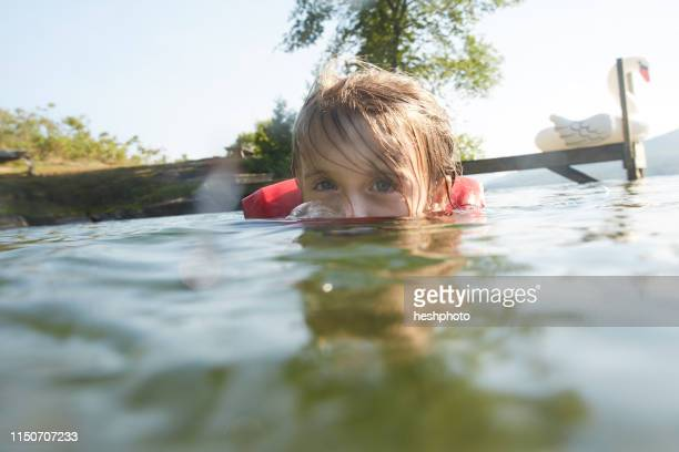 girl swimming and playing in lake - heshphoto stock pictures, royalty-free photos & images