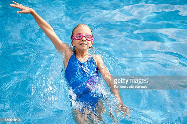 Girl swimming backstroke in pool