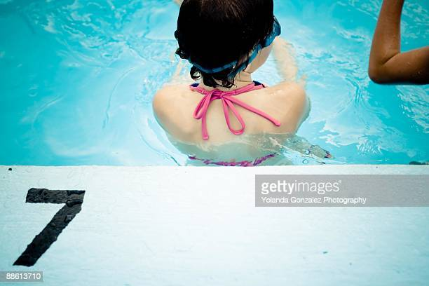 Girl swimming in community pool's deep end