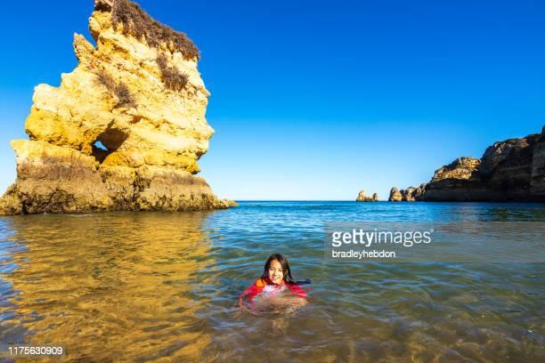 ragazza che nuota nelle fredde acque turchesi della spiaggia di praia dona ana in algarve, portogallo - paesaggio marino foto e immagini stock