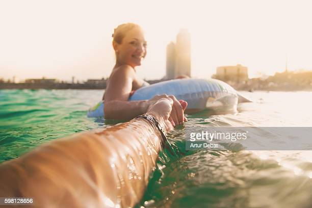 girl swimming on inflatable ring pad on mediterranean sea with boyfriend taking his hand and taking picture from personal perspective with the skyline of the barcelona city on sunset during summer time without stress and relaxing times. follow me. - agosto fotografías e imágenes de stock