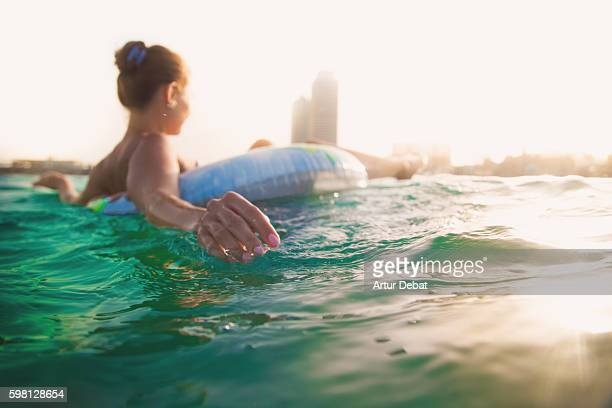 girl swimming on inflatable ring pad on mediterranean sea with the skyline of the barcelona city on sunset during summer time without stress and relaxing times. - auf dem wasser treiben stock-fotos und bilder