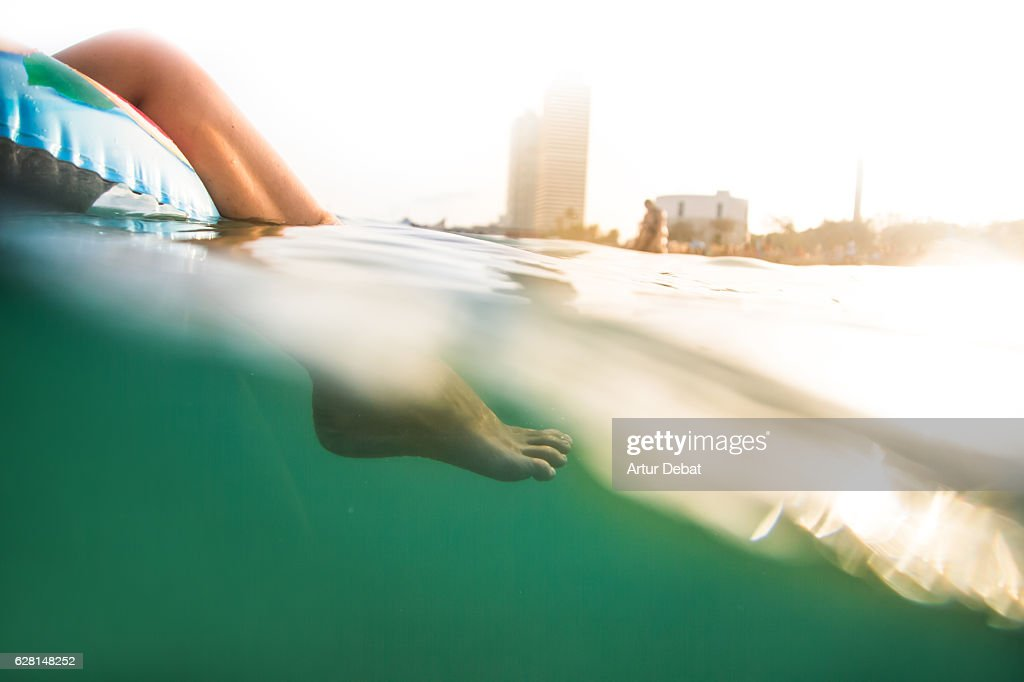 Girl swimming on inflatable ring pad with underwater view on Mediterranean Sea with the skyline of the Barcelona city on sunset during summer time without stress and relaxing times. : Stock Photo