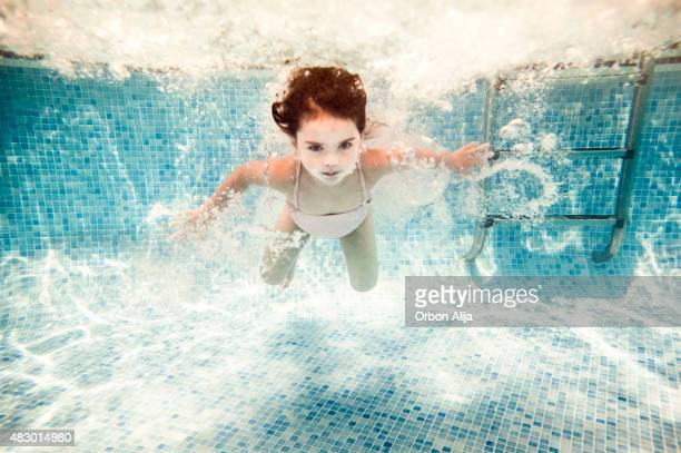 Girl swimming under water in a pool