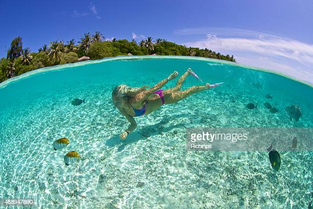 Girl swims in tropical lagoon with fish and resort