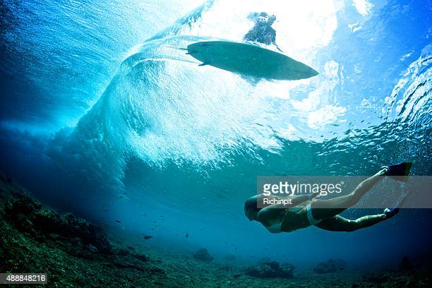 Girl swims under the wave while surfer is sihlouetted above