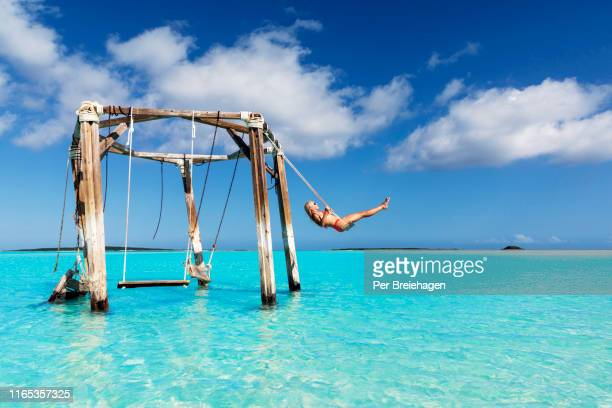 a girl swinging at cocoplum beach_exuma_bahamas. - バハマ ストックフォトと画像