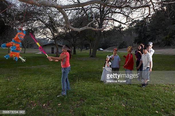 Girl (10-11) swinging at donkey pinata, friends (5-14) watching