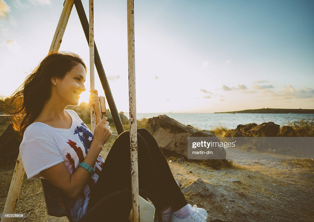 Girl swinging at sunset : Stock Photo