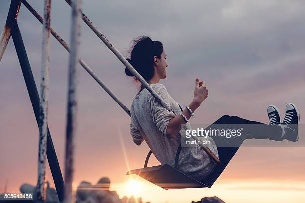 Girl swinging at sunset