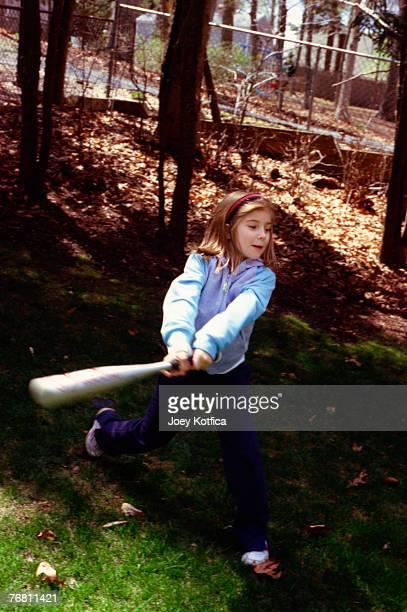 Girl swinging baseball bat
