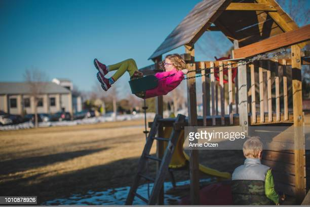 Girl Swinging from a backyard swing set