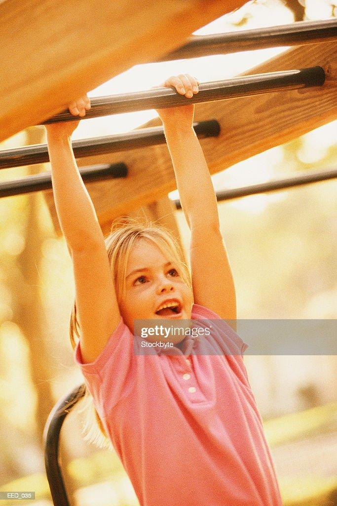 Girl swinging from horizontal bars on jungle gym : Stock Photo