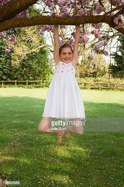 girl swinging from tree in backyard - schommelen bungelen stockfoto's en -beelden
