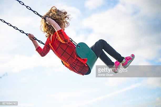 girl swinging high into the air - swinging stock pictures, royalty-free photos & images