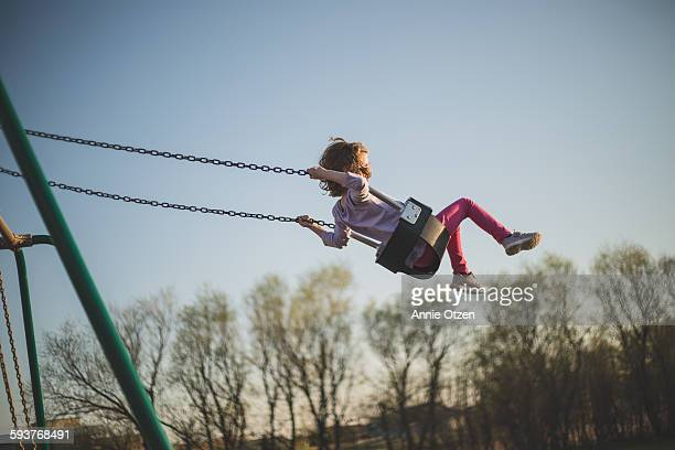 girl swinging high into the sky - swinging stock pictures, royalty-free photos & images