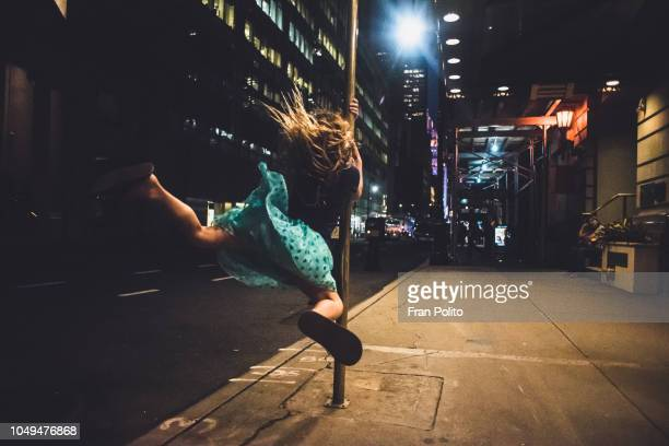 a girl swinging on a pole in new york city - free up skirt pics stock photos and pictures
