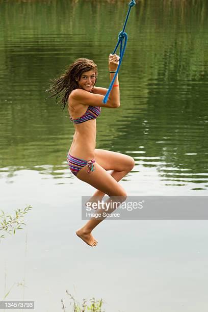 Petite fille se balancer sur une corde autour d'un lac