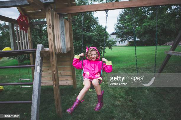 Girl swinging on a swing on a rainy day