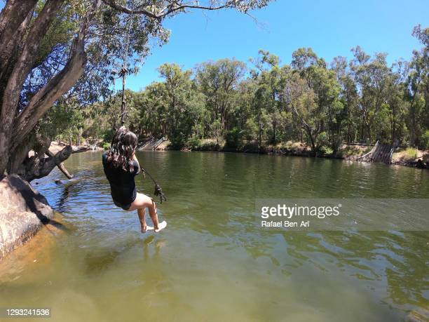 girl swinging on a tree swing into river - rafael ben ari - fotografias e filmes do acervo