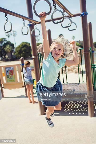 Girl swinging on jungle gym