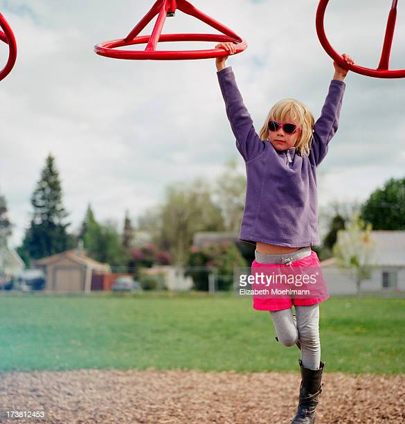 girl swinging on monkey bars - monkey shoes stock photos and pictures