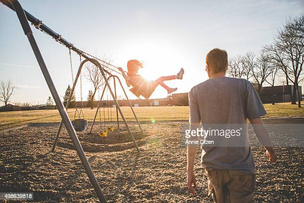 Girl swinging on swing set while father walks towards her