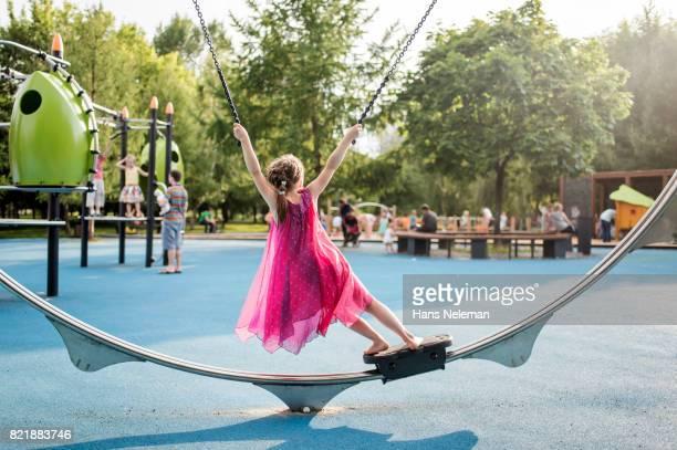 girl swinging on the carousel - ショッキングピンク ストックフォトと画像
