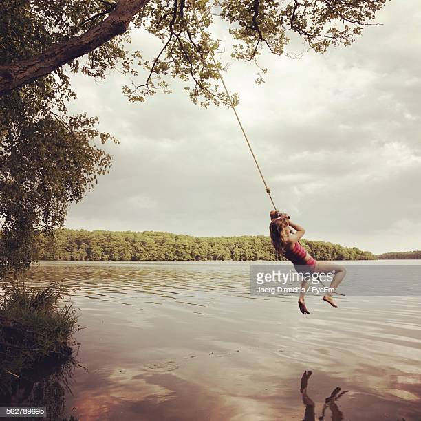 Girl Swinging Over Lake Against Sky