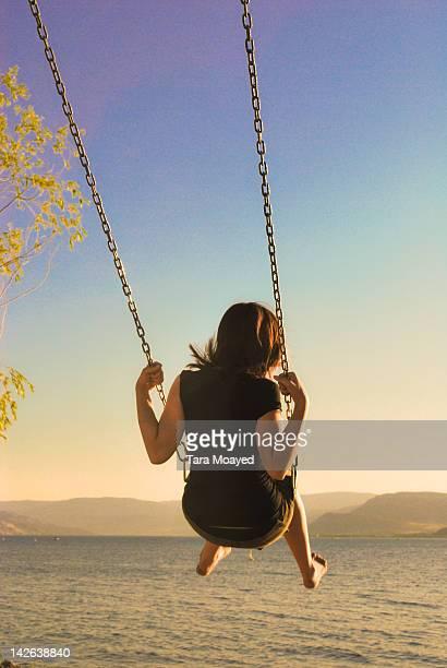 girl swinging over lake okanagan - kelowna stock pictures, royalty-free photos & images
