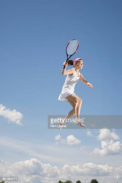 Girl swinging tennis racquet, airborne