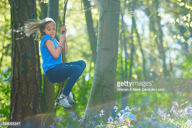 Girl swinging through trees in bluebell forest, Hallerbos, Brussels, Belgium