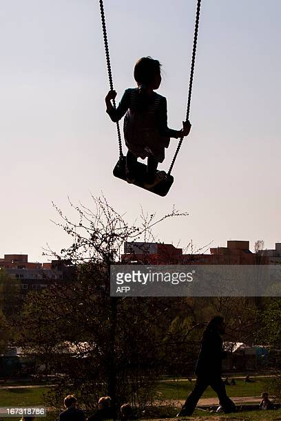 Girl swings at the Mauerpark in Berlin on April 24, 2013. Temperatures in the German capital reached around 19 degrees Celsius. AFP PHOTO / CARSTEN...