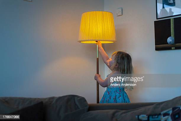 girl switching on lamp in living room