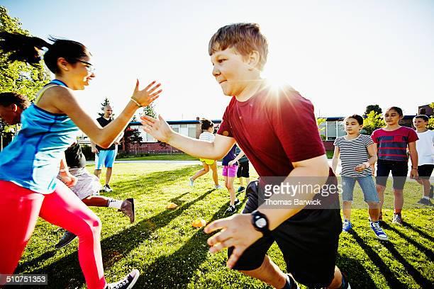 Girl tagging boy in relay race on grass field