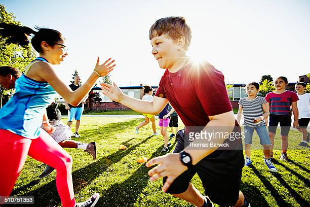 Girl tagging boy in relay race on grass field