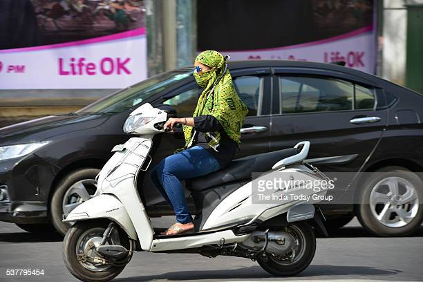 Girl take precaution against the heat waves while riding on a scooter in New Delhi