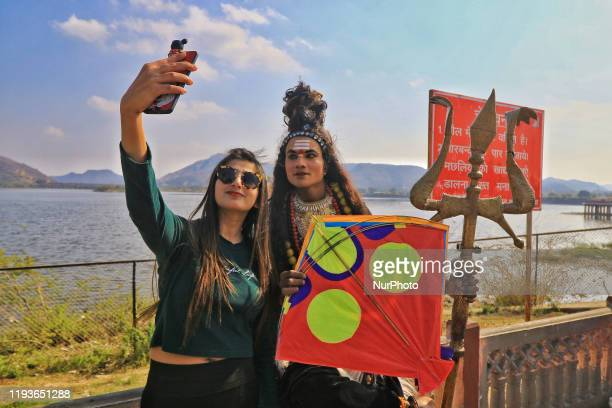 Girl take selfie with dress up artist during the Kite Festival on the occasion of the Makar Sakranti Festival at Jal Mahal in Jaipur, Rajasthan,...