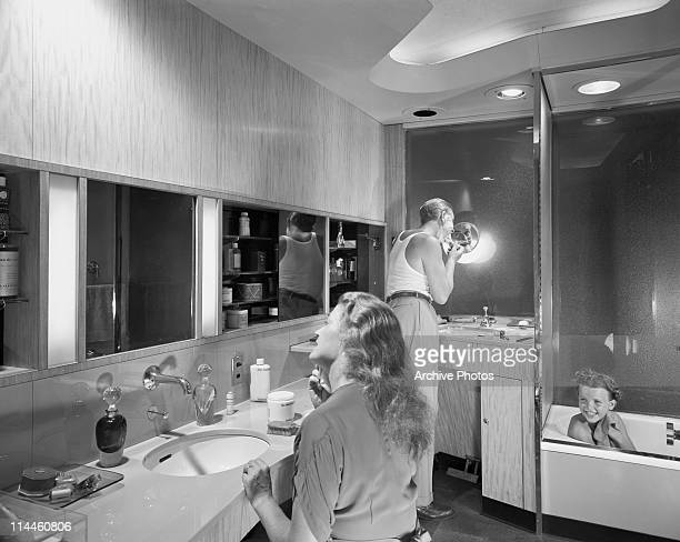 A girl takes a bath as her father shaves and her mother brushes her teeth in a spacious fitted bathroom circa 1955