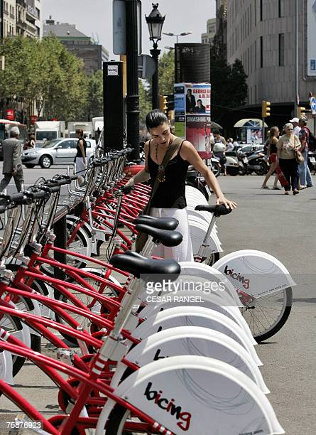 A girl takes a 'Bicing' bike for a ride a new shared bicycle service 18 July 2007 in Barcelona 'Bicing' provided since the end of March around 200...