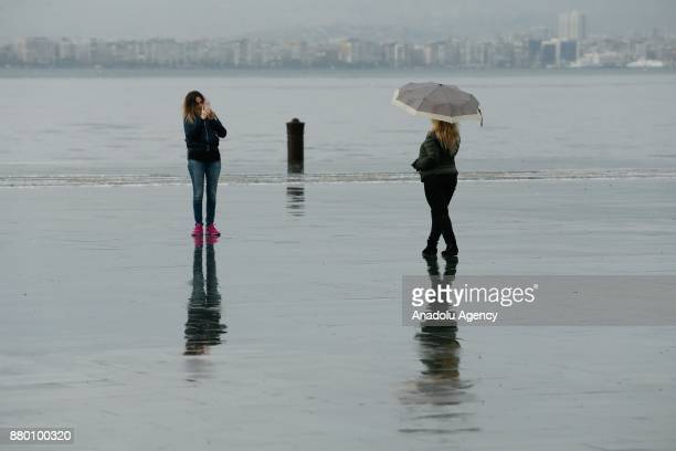 A girl takes a photo of another girl with an umbrella as they stand on a wet floor after heavy rainfalls hit Izmir Turkey on November 27 2017 People...