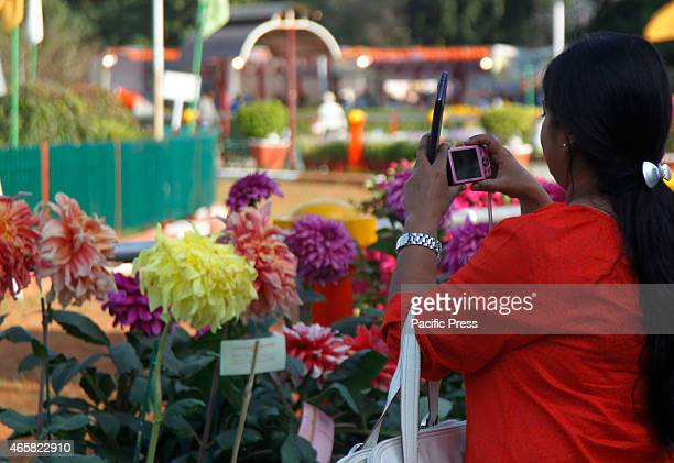 A girl takes a photo to flowers during two days flower show in Allahabad At this time Allahabad was a highly peaceful city and one reason for this...