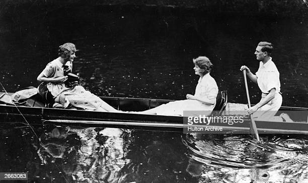 A girl takes a photograph of her friends with a large Kodak camera while sailing in a punt