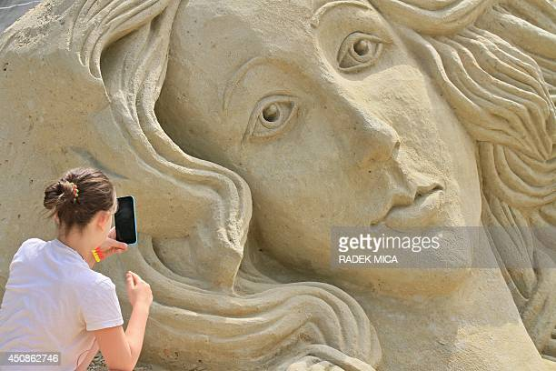 A girl takes a photograph of the sand sculpture 'Botticelli Venus' during the Sand festival in Lednice south Moravia 50 km south of Brno on June 19...