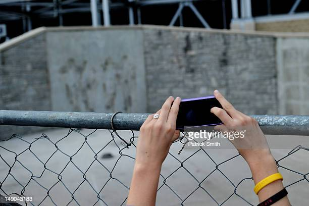 A girl takes a picture at the site in which the statue of former Penn State University football coach Joe Paterno stood sits empty after it was...