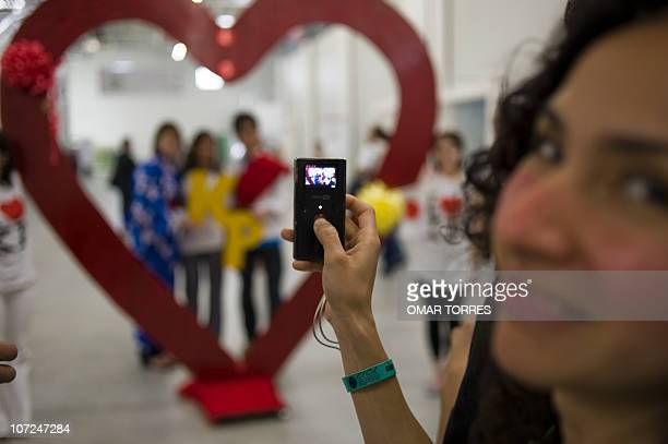 A girl takes a picture during a demonstration of different enviromental organizations demanding Japan to keep in the Kyoto Protocol inside the Cancun...