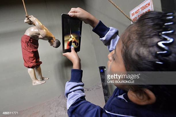 A girl takes a picture of a dummy depicting a man tortured on the pulleyduring a school visit to the Museum of the Inquisition in Lima Peru on April...