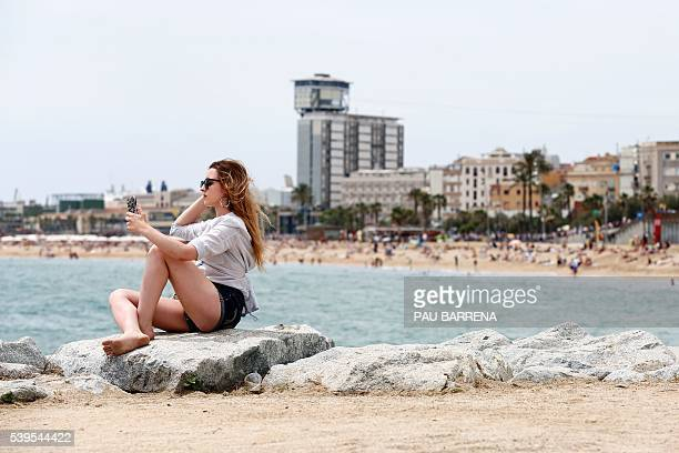 A girl takes a selfie at the Barceloneta's beach in Barcelona on June 12 2016 / AFP / PAU BARRENA