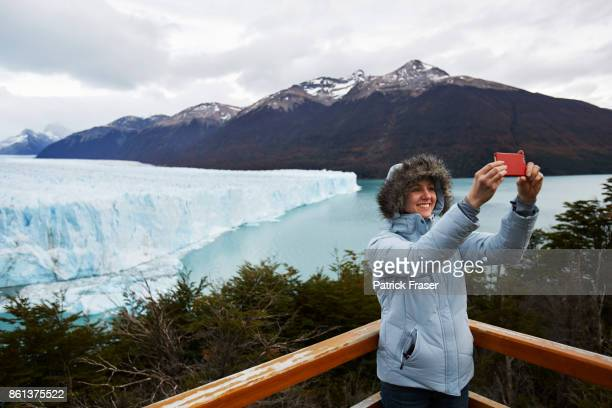 Girl takes a selfie in front of Perito Moreno Glacier