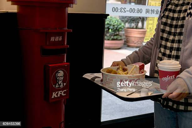A girl takes her food walking past a KFC mailbox As the largest restaurant chain in China with more than 7000 outlets KFC makes new strategy...